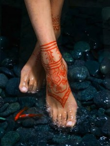 Beautiful red henna tattoo on woman foot.