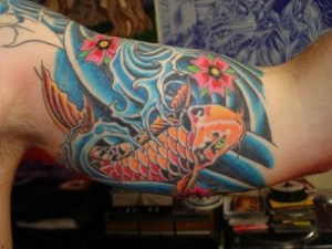 An orange koi fish tattoo in the splashing water on a young man's sleeve.