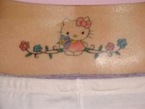 Hello Kitty lower back tattoo with flowers.